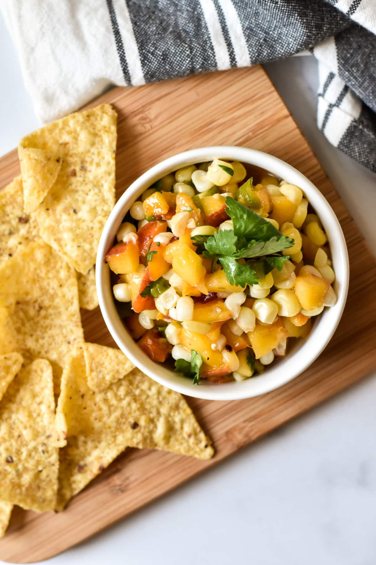 dish of peach, corn and chile salsa with chips on a wood cutting board