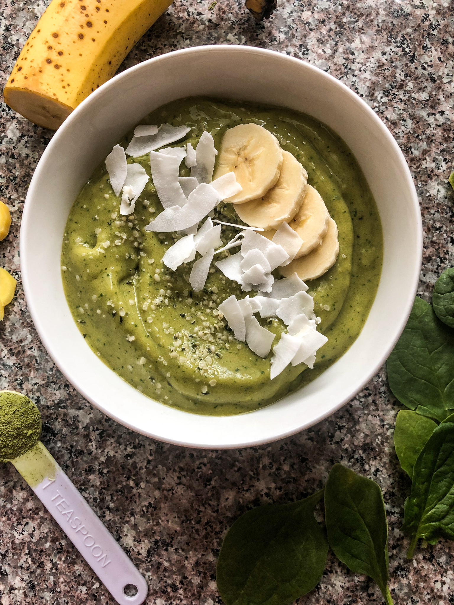 matcha green tea ginger smoothie bowl with toppings scattered around