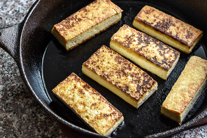 tofu browning in a cast iron skillet