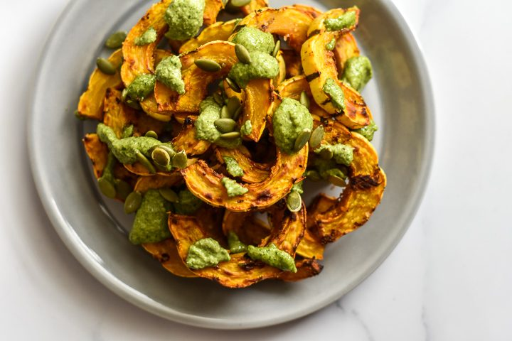 delicata squash with pesto and pepitas on a plate