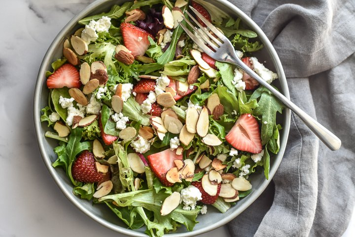 salad with strawberries, goat cheese and sliced almonds in a bowl