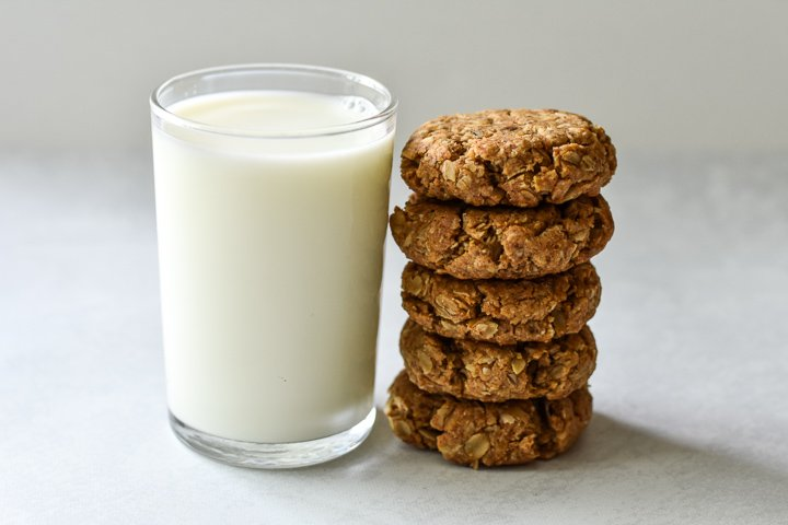 stack of vegan oatmeal cookies next to a glass of milk