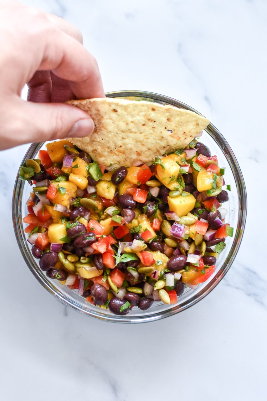 dipping a tortilla chip in mango black bean salsa