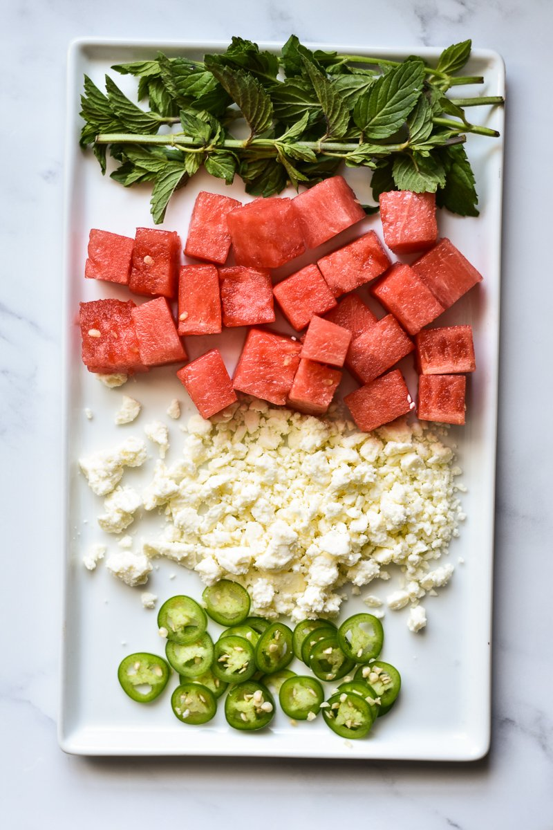 mint, watermelon, feta and serrano peppers on a rectangle plate