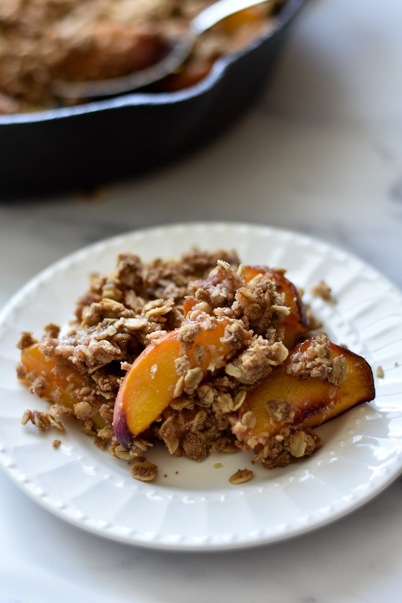 small plate with a serving of cardamom peach crisp