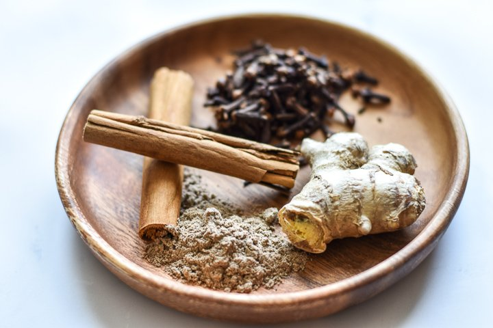 plate with ginger, cardamom, cloves and cinnamon sticks