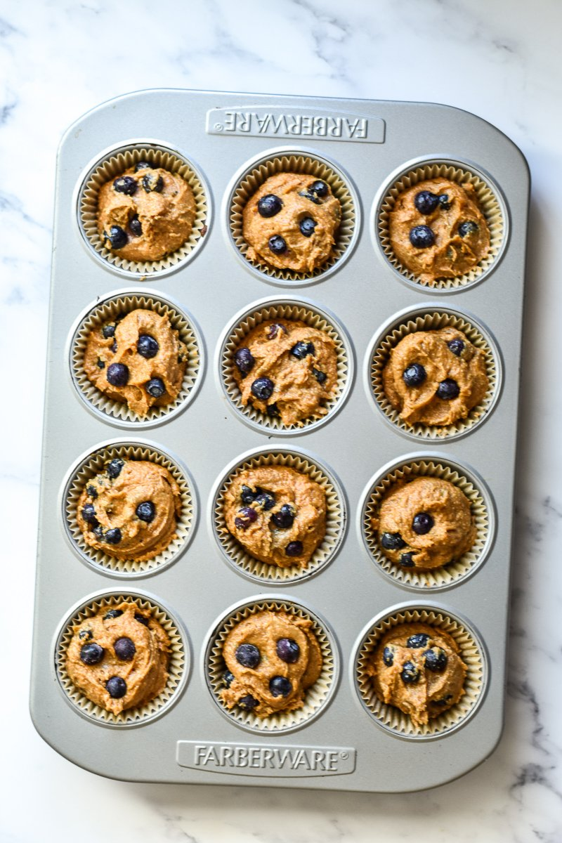 pumpkin blueberry muffins in a muffin pan