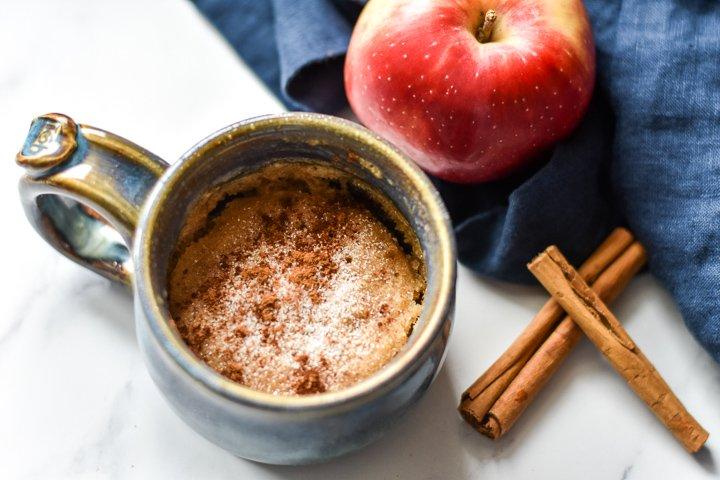 vegan mug cake with an apple and cinnamon sticks