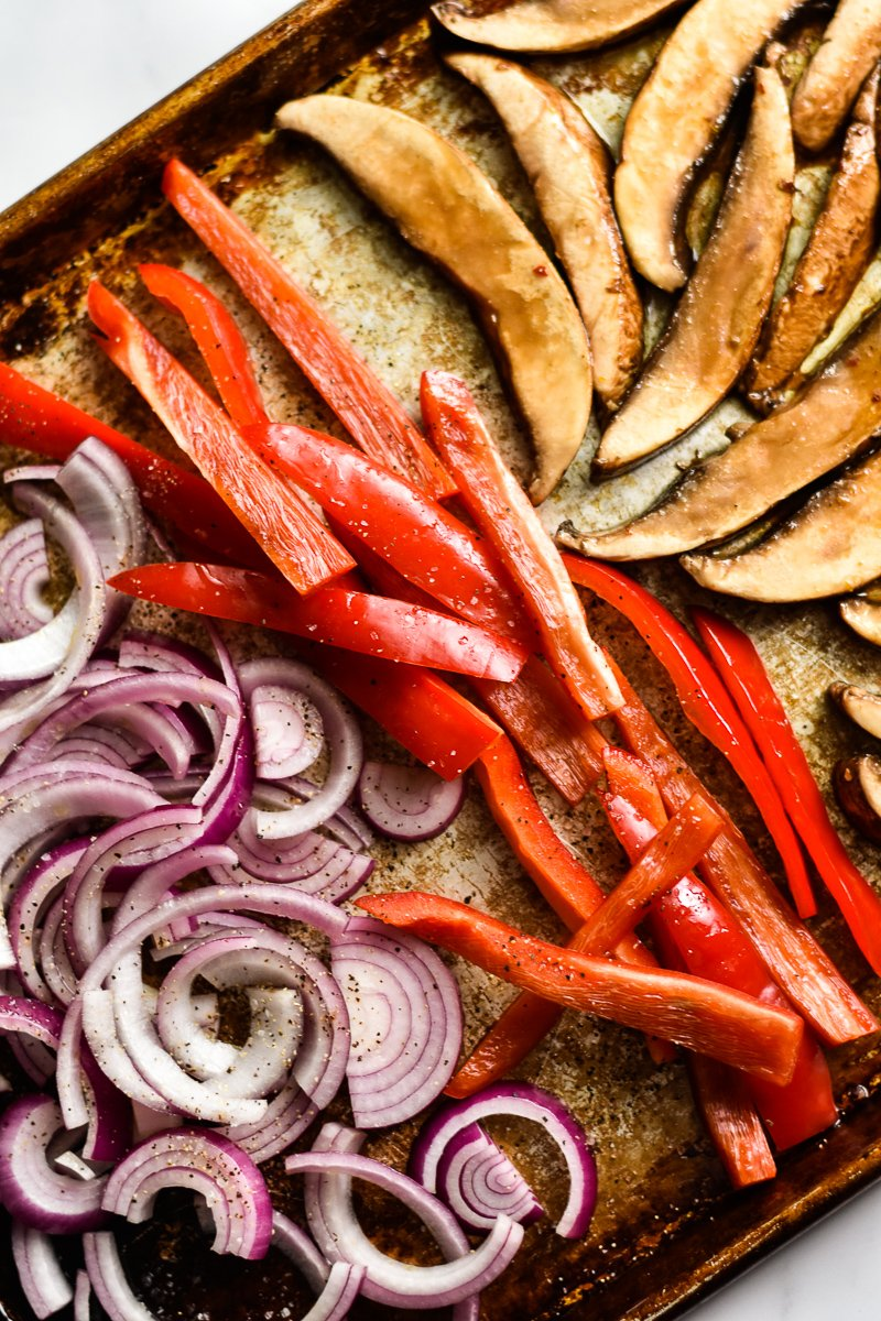 sliced mushrooms, red bell peppers and onions on a sheet pan
