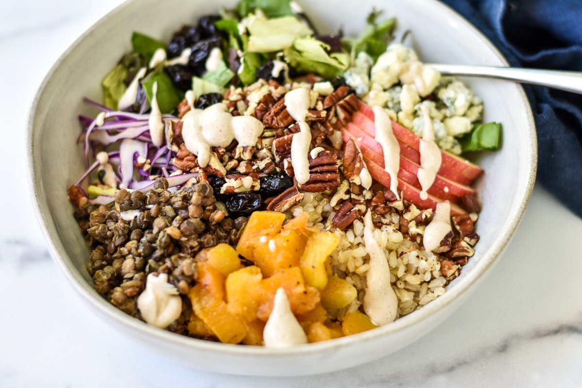 autumn rice bowl drizzled with creamy tahini dressing