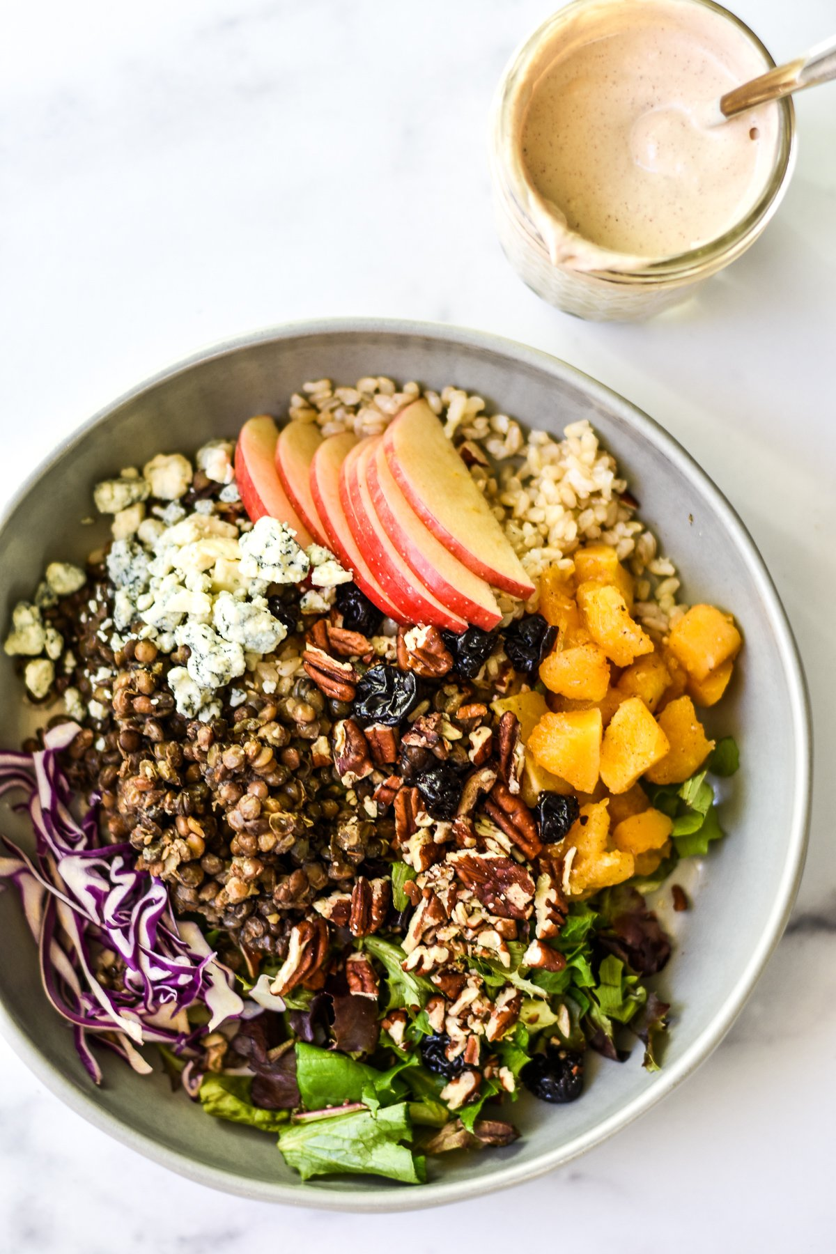 autumn rice bowl with a jar of creamy dressing on the side