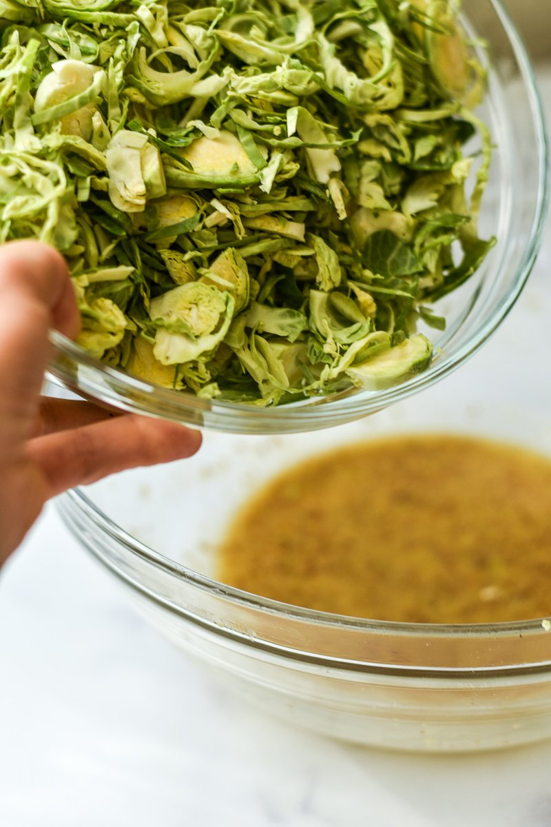 dumping brussels sprouts into dressing