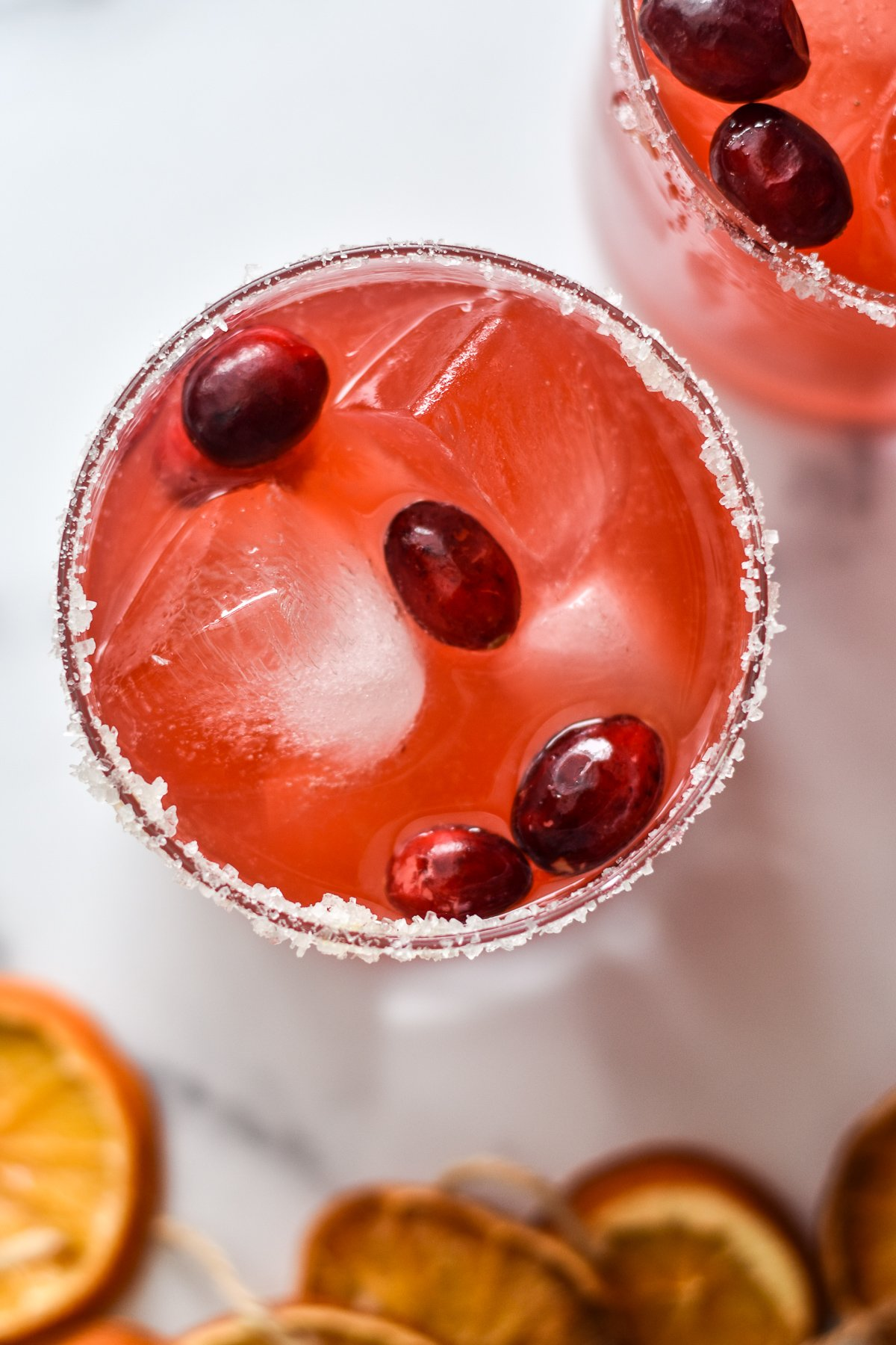 fresh cranberry ginger margarita in a glass with cranberry garnish