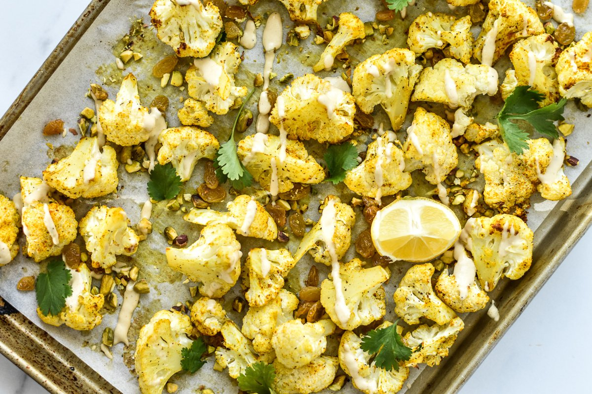roasted cauliflower with tahini drizzle on a sheet pan