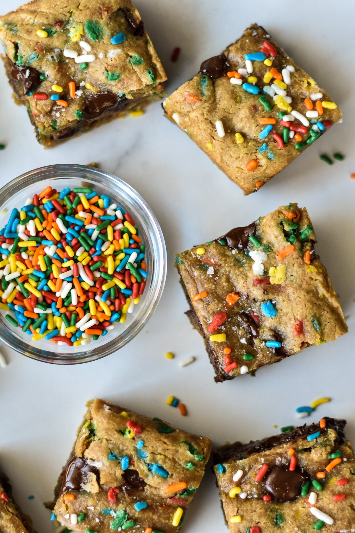 vegan blondies with sprinkles and chocolate chips and an extra bowl of sprinkles