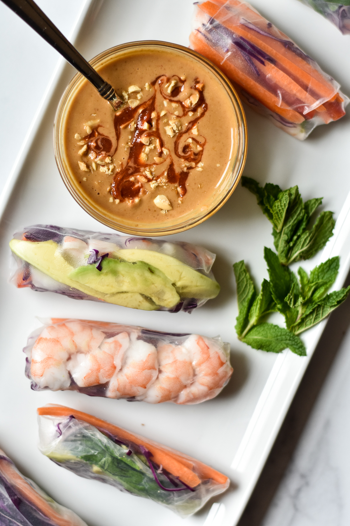 summer rolls on a platter with peanut dipping sauce and mint leaves