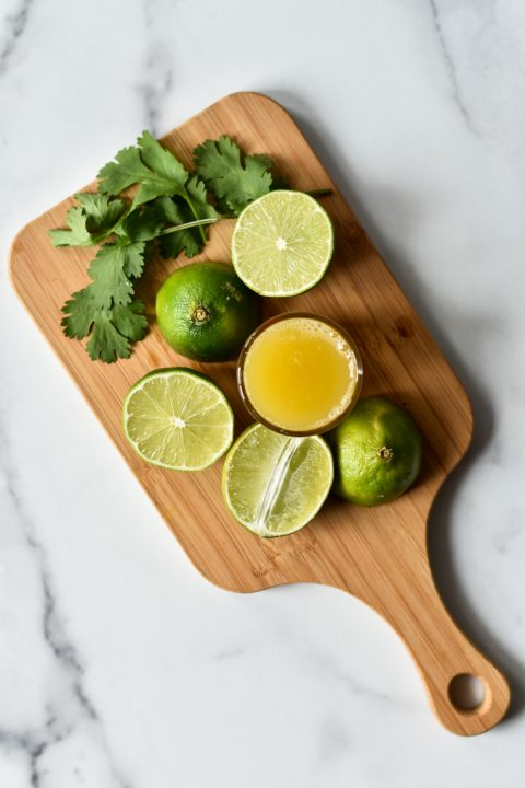 limes cilantro and pineapple juice on cutting board