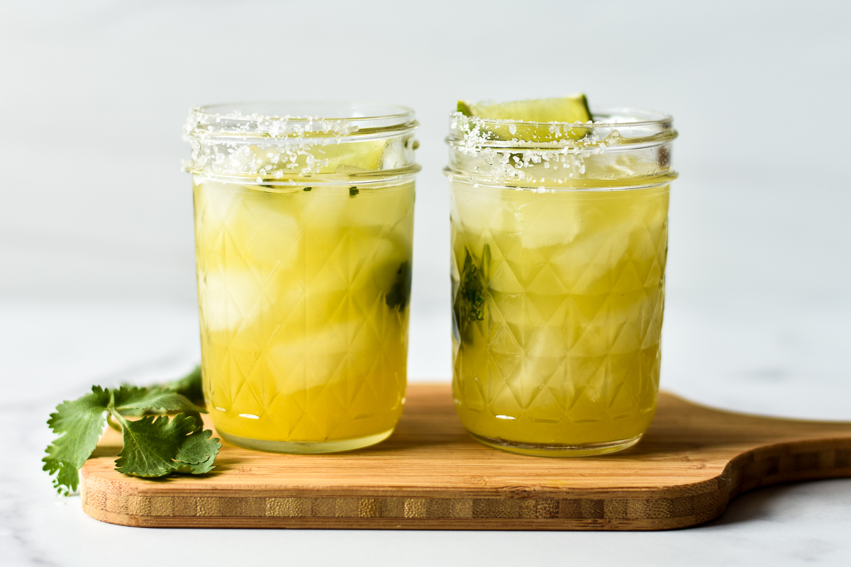 two margaritas on a wooden cutting board with cilantro garnish