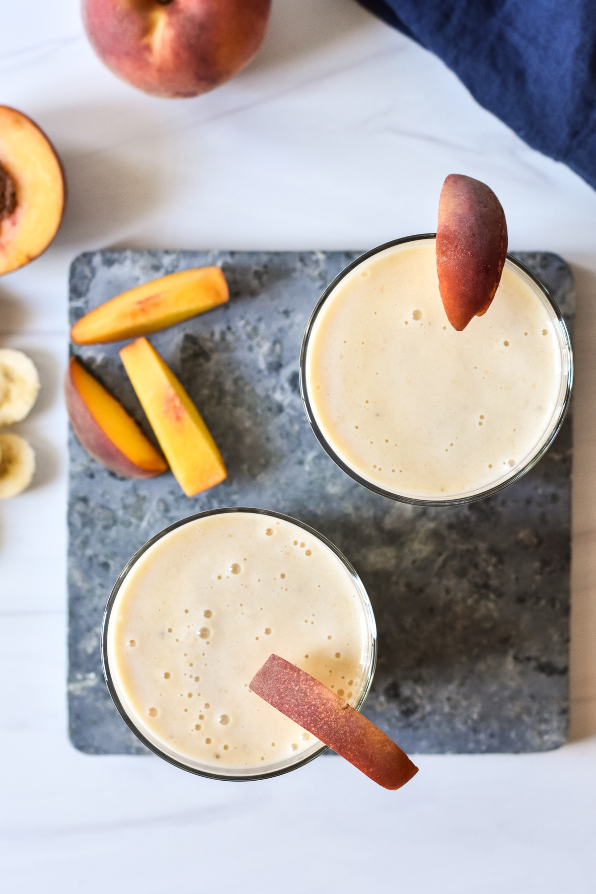 two smoothies with peach slices on rim