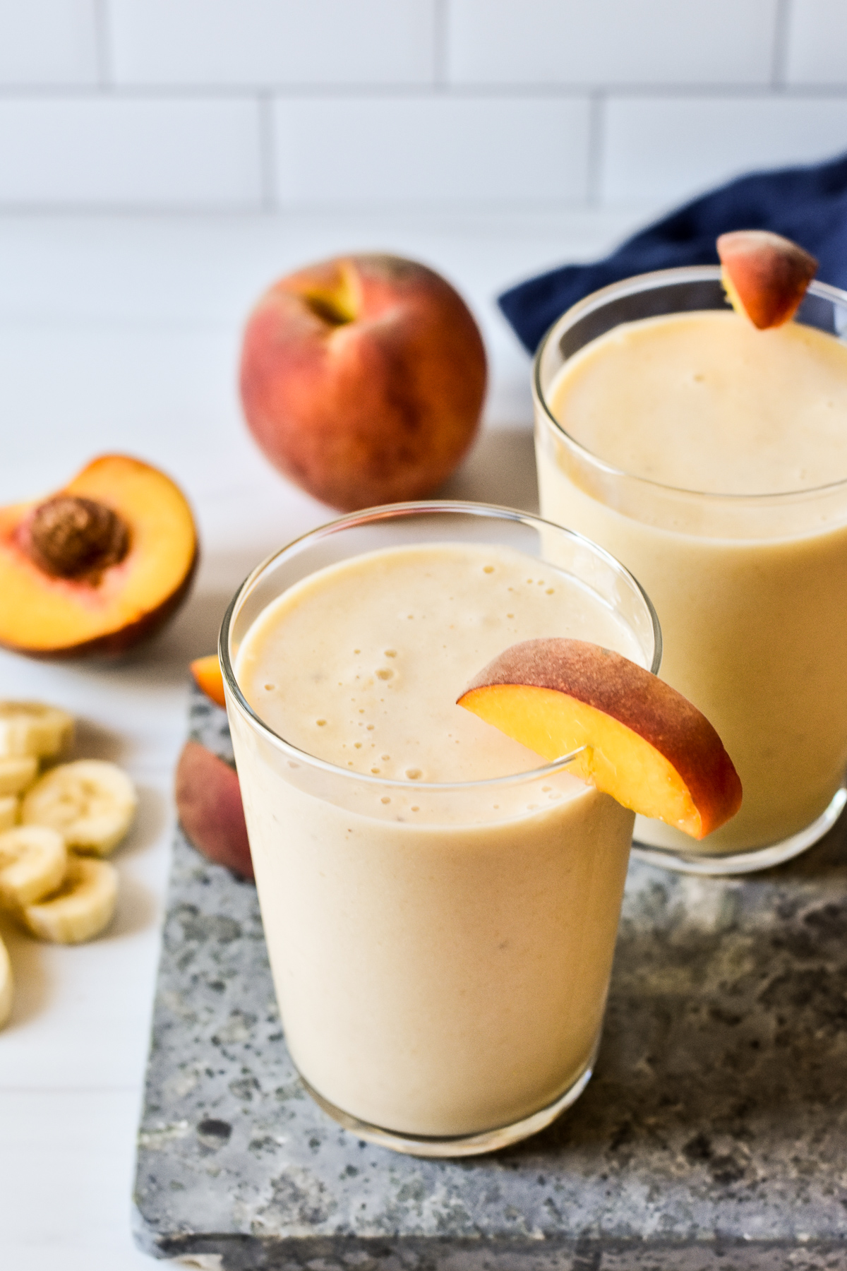 banana peach smoothies in glasses with peaches in the background