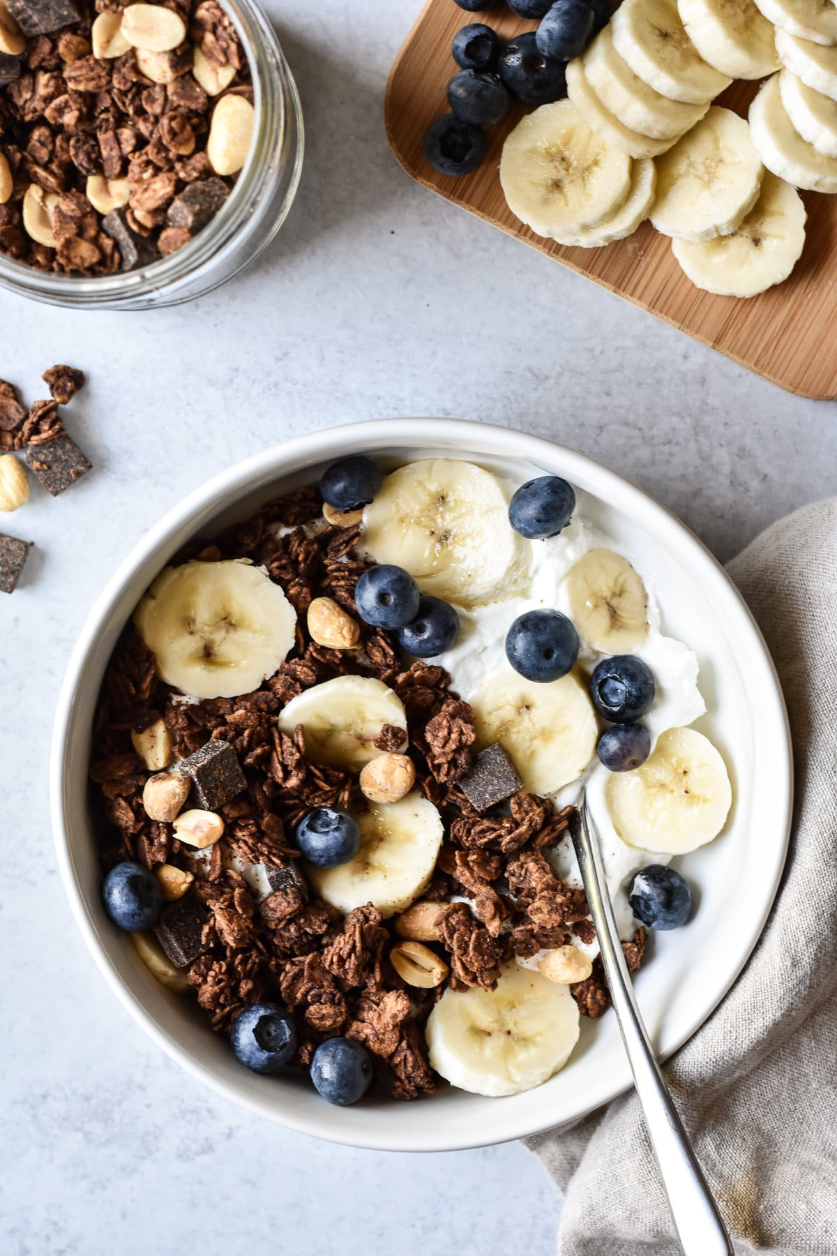 bowl of yogurt with chocolate peanut butter granola and bananas and blueberries.