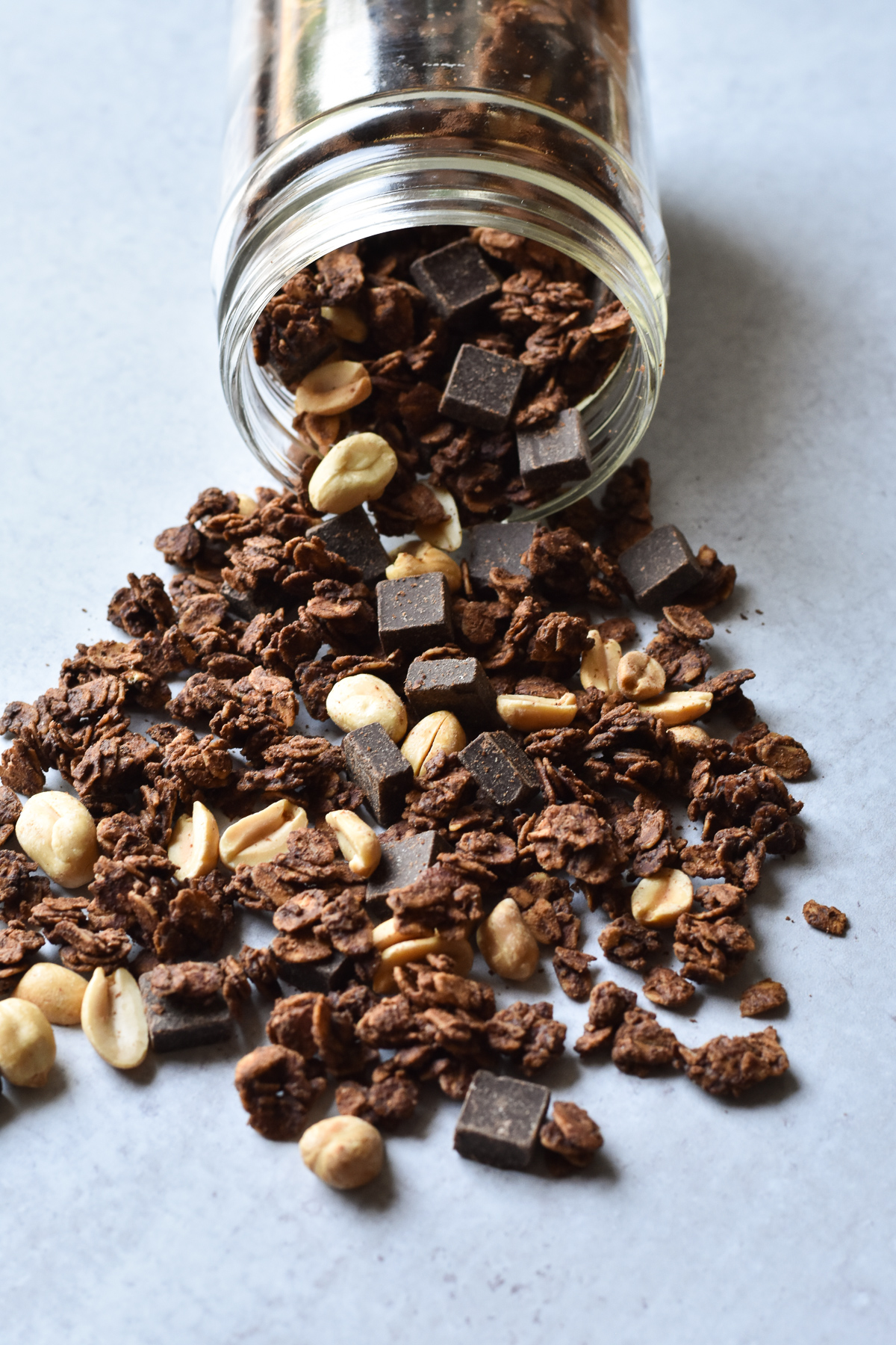 jar of granola with chocolate and peanuts spilling out