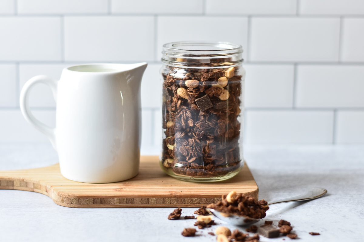 jar of chocolate peanut butter granola next to milk