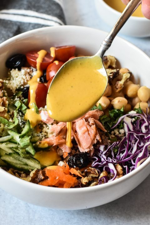 nourish bowl with a spoon with sauce over top