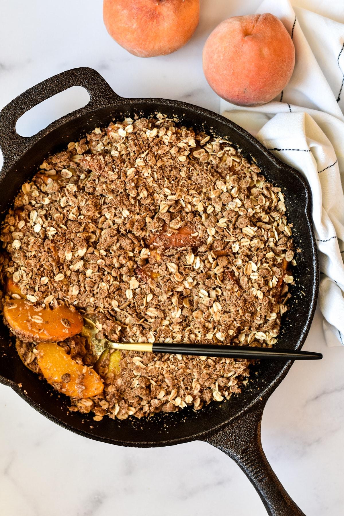 gluten-free peach crisp in a cast iron skillet