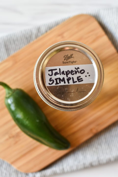 jalapeño on a wooden cutting board with jar