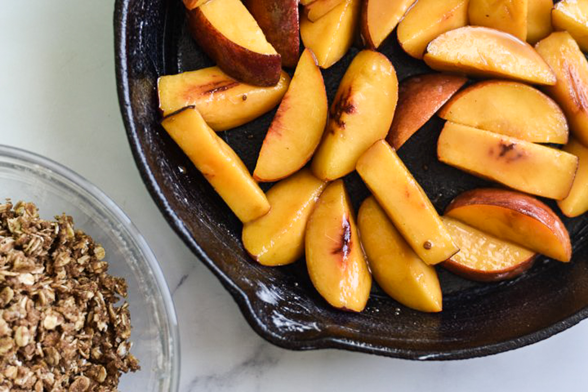 glossy peaches in cast iron skillet with crumble topping in a separate bowl
