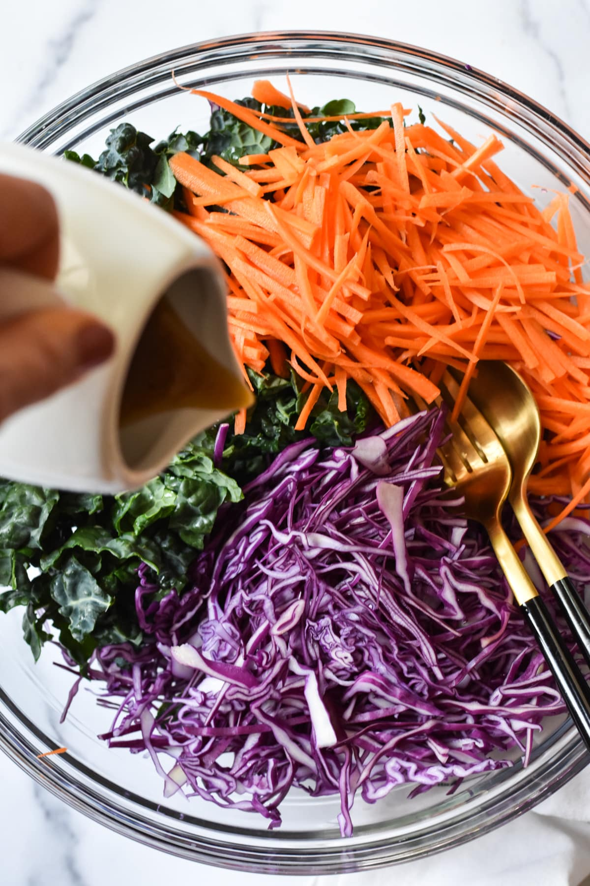 purple cabbage, carrots and kale in a bowl with dressing pour