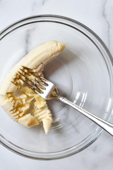 mashing a banana in a bowl